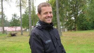 En man med mörk jacka och kort hår står utomhus på gräsmatta och ser in i kameran. Björkar i bakgrunden.
