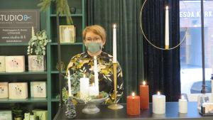 En kvinna med munskydd står bakom ett bord med ljus (ledljus) som hon säljer.