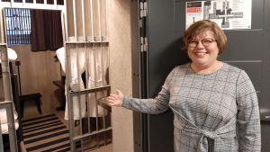 Anu Salminen, en dam med ljust hår, glasögon och en grårutig klänning, håller ut ena armen och bjuder in dig i en cell som är bevarad i ursprungligt skick i det gamla fängelset på Kakolabacken i Åbo.