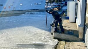 Sjöbevakare Patrik Neem slår mot isen med ett metallspett för att testa om den håller.