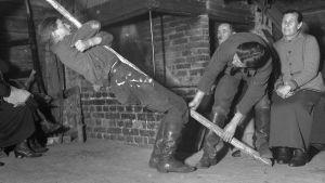 """En man leker leken """"stiga upp med stången"""". Bilden är tagen 1935 i Bromarf, Rilaks."""