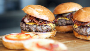 Tre hamburgare på en köksbänk.
