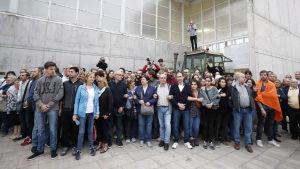 Människor står i armkrok utanför en vallokal i Girona för att stoppa polisen. Bakom människorna står en traktor parkerad framför dörren.