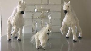 Kolme valkoista yksisarvisfiguuria pöydällä.