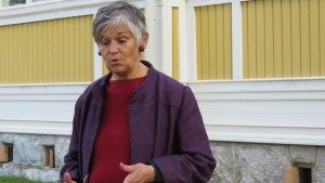 En kvinna med grått kort hår står framför ett gulmålat trähus (uncan i Ekenäs). Hon ser inte in i kameran utan ner mot händerna, som hon viftar med och förklarar något.