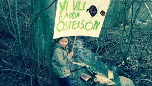 pojke står vid ett dike med ett plakat
