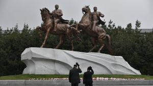 Två män visar sin respekt inför statyer av landsfadern Kim Il Sung och sonen och arvtagaren Kim Jong Il