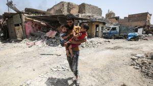 Man bär på två barn mitt bland ruiner i Mosul.