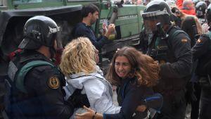 Kravallpolis i Barcelona bär bort två kvinnor utanför en vallokal.