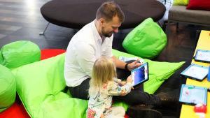 En förälder och ett barn spelar på en iPad