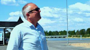 Företagare Tom Nylund i profil en solig sommardag i Norra hamnen i Ekenäs. Hav i bakgrunden.