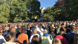 Hundratals personer står och lyssnar på ett tal.