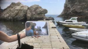 En turistguide visar en bild på en scen från TV-serien Game of Thrones som är inspelad på samma plats som bilden är tagen.