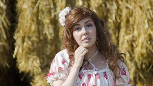En kvinna klädd i så kallade Lolitakläder - en fluffig vit och rosa klänning med spetsar på. Hon har också blommor i håret. Hon står framför en massa höbalar.