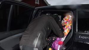 en man, pappa,  spänner fast bilbälte på barn i baksätet av en bil