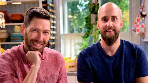 Kaksi parrakasta miestä hymyilevät.