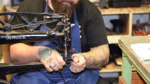 En man med tatuerade armar som syr i läder på en gammal symaskin. Man ser inte ansiktet på mannen.