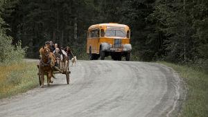 Evakkojen hevoskärry ja keltainen linja-auto hiekkatiellä.