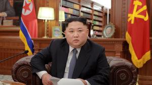 Kim Jong-Un höll sitt tal från en bekväm fåtölj  i vad som verkade vara hans personliga arbetsrum eller bibliotek