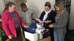 Fyra kvinnor står samlade runt en låda med begangade kläder.