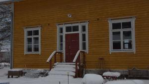En gul, gammal trävilla  med stentrappa. Huset i hyfsat skick. Vinter och snö.