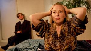 Milla Kangas (Sarah) ja Lauri Tilkanen (Richard). Richard istuu lattialla, Sarah haroo hiuksiaan vuoteella istuen.