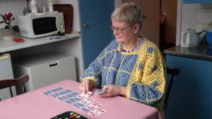 Gunilla Löfman sitter vid sitt köksbord och lägger patiense