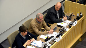 Siv Sandberg, Olavi Kaleva och Göran Honga sitter alla tre vid samma sida av ett bord och blickar framåt. De är fotade uppifrån.