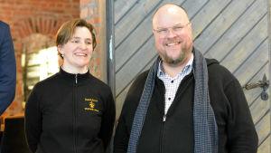 En kvinna klädd i svart bredvid en man i rutig skjorta och svart tröja. De står framför en dörr och ler.