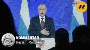 Vladimir Putin som håller tal visas på en skärm framför en publik som syns som skuggor.