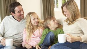 Familj med två vuxna och två barn ungås i soffan.