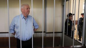 Frode Berg bakom galler och två uniformsklädda personer intill.