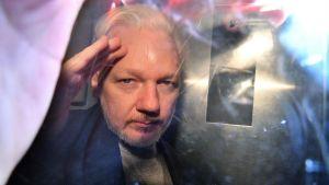 Julian Assange gestikulerar till fotografer då han lämnar domstolen i London den första maj 2019, efter att ha dömts till 50 veckor i fängelse.