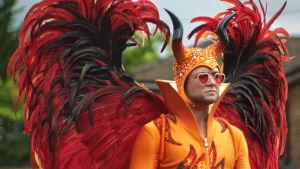 Elton John (Taron Egerton) iklädd en paljettbeströdd orangedräkt med stora röda vingar och en mössa med paljetter och horn.