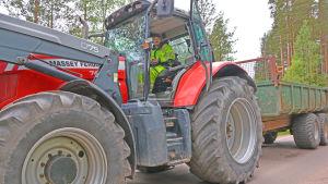 Man med gul rock sitter i en stor traktor på en sandväg.