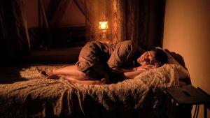 Wanda Dubielin näyttelemä Aliide Truu makaa vuoteella takkimekko yllään. Sängyllä on pitsipeitto, ikkunassa pitsiverhot.