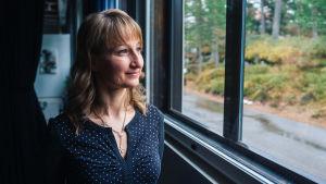 Tanja Poutiainen står i blå skjorta med vita prickar och tittar ut genom ett fönster.