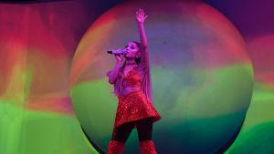 Laulaja Ariana Grande seisoo värikkään screenin edessä lavalla toinen käsi ilmaan nostettuna. Toinen käsi pitelee mikkiä suun edessä. Päällään hänellä on punaiset korkeat saappaat ja punainen paljettiasu.