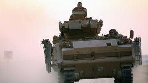 Turkisk stridsvagn som deltar i invasionen av nordöstra Syrien. Två huvuden syns titta fram ut stridsvagnen.