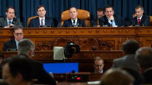Ordföranden för representanthuset underrättelseutskott, demokraten Adan Schiff  i mitten och republikanernas ledande medlem i utskottet Devin Nunes (andra från höger) under de tv-sända förhören  den 13 november 2019.