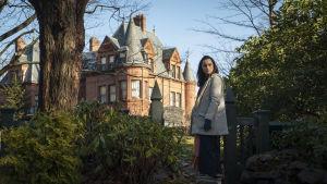 Marta (Ana de Armas) står vid en port och ser bakom sig. I förgrunden syns ett stort gammalt hus.