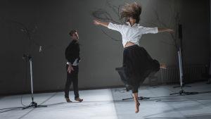 En kvinna i vit skjorta gör ett danssprång. I bakgrunden går en svartklädd man.