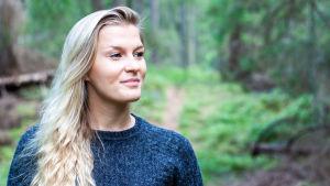 En kvinna iklädd en stickad tröja. Hon står i en skog och ser rofylld ut.