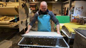 Andrea Clementi formar med säker hand pappersmassan till en jämn yta på ett finmaskigt nät, vilket är det svåraste arbetsmomentet.