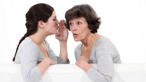 Ung kvinna viskar i örat på en äldre kvinna som ser förvånad ut