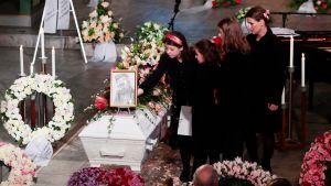 Ari Behns döttrar och ex-fru står vid Behns vita kista. Kistan omges av ett hav av blommor.