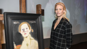 Laura Birn invid ett självporträtt av Helene Schjerfbeck.