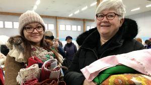 Marjo och Merja Sartovuo håller i sina textilfynd, tyger och poppana.