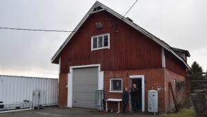 En man och en kvinna står strax utanför en stor röd ladugård i tegel och rödmyllad brädfodring. Ute på landet, tidig vår. Ingen snö.