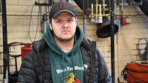 En man står i en hall iklädd keps och jacka.